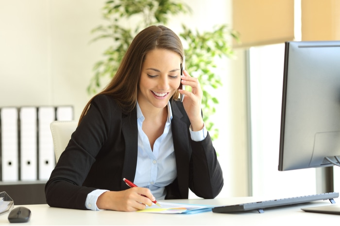 Happy businesswomen talking on cell phone and taking notes at a desk in an office