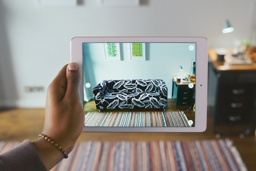 Ikea's augmented reality technology on an tablet showing a customer what one of their couches would look like in the customer's home.