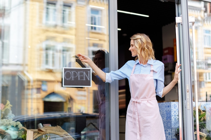 Women in apron holding an open sign up at a store front window.