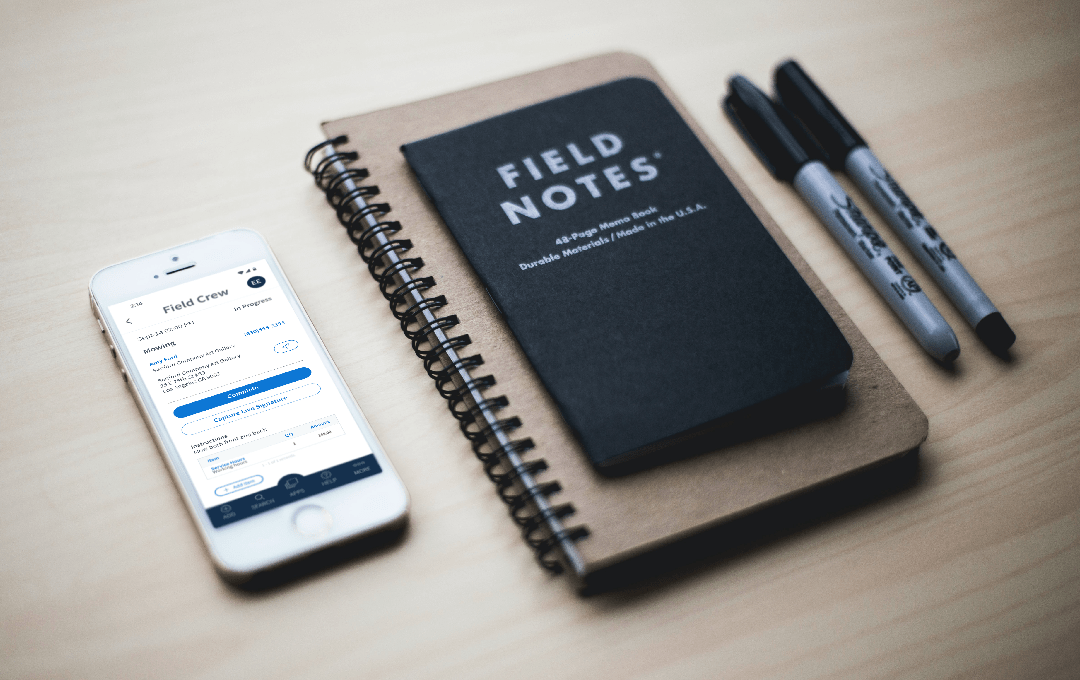 Method:Field Services mobile app on a white iPhone alongside a black field notes notebook and two black Sharpie markers.