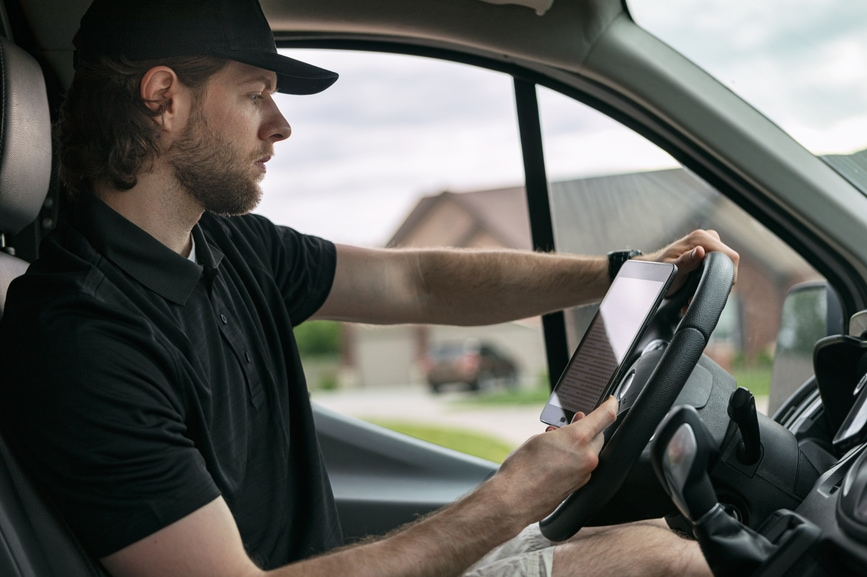 Man stops over and checks his work order for next job and route