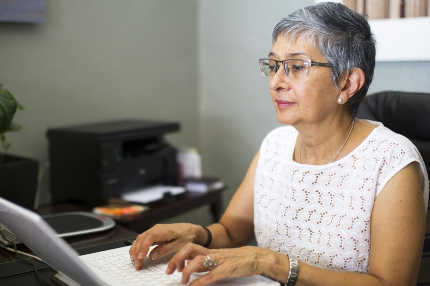 woman doing invoices on laptop in office