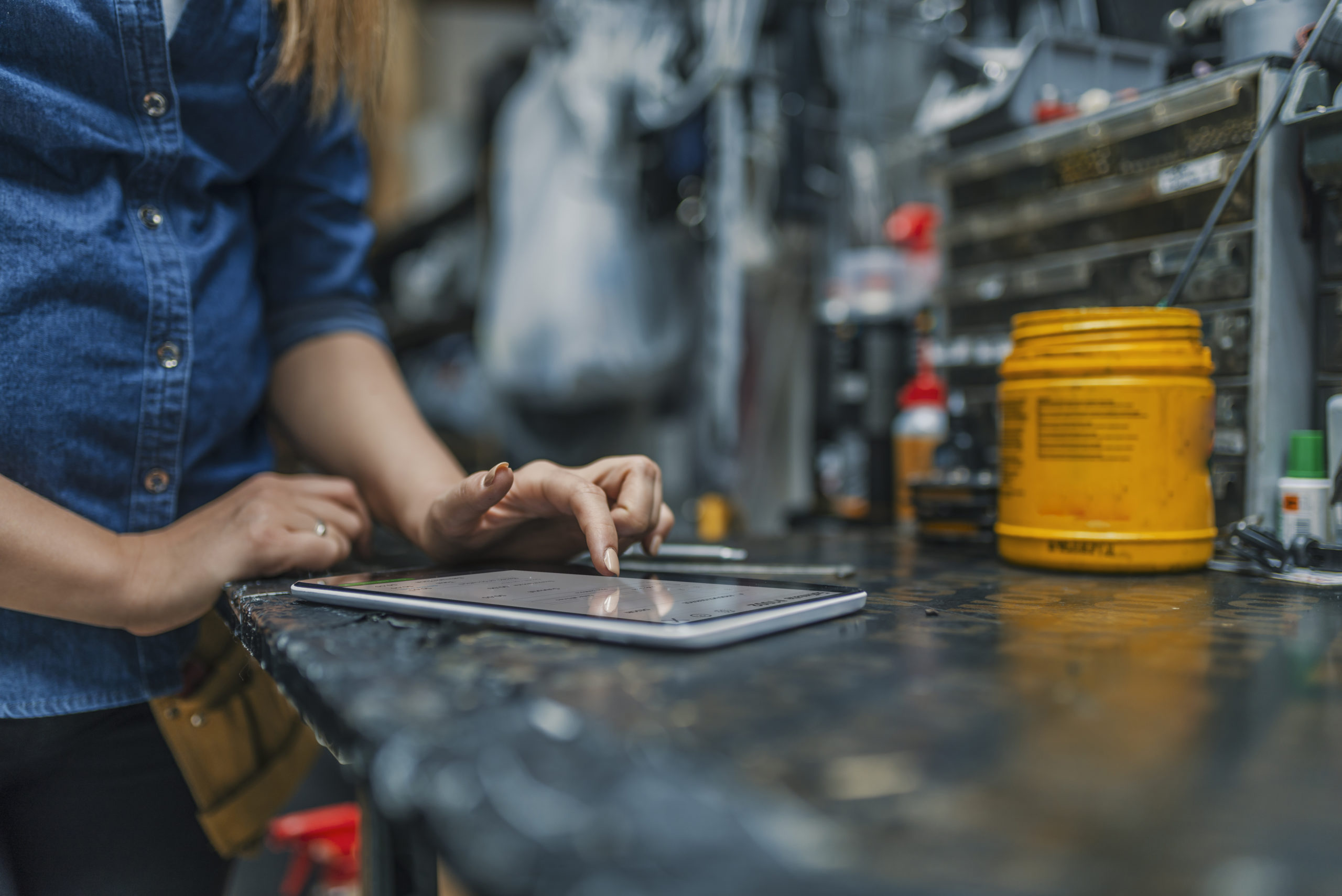 Mechanic uses QuickBooks Online on her tablet at work.
